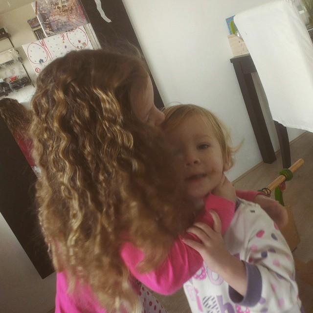 Nova krijgt een kus van haar krullenbol zus