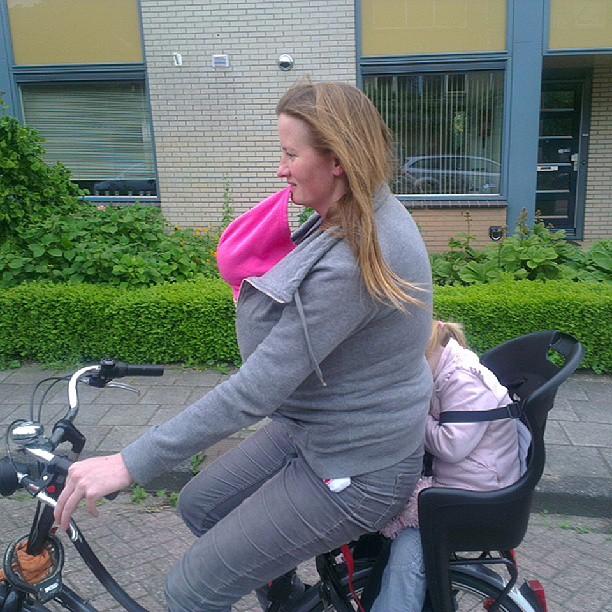Na een dagje Rijksmuseum zijn beide meiden uitgeteld en Edith probeert ze op behendige wijze op de fiets overeind te houden..